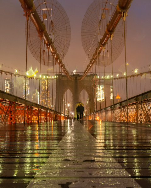 Couple sharing an umbrella in the rain on the Brooklyn Bridge.