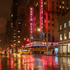 Radio City Music Hall seen from 6th Avenue in the rain during the blue hour.