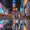 View of Times Square and two passing taxis through a Lensball reflected in a mirror with snowfall.