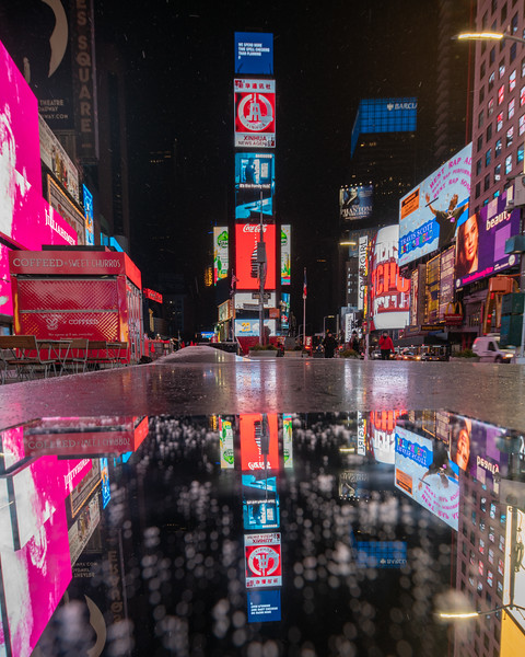 Times Square with its reflection in a mirror during a light snowfall.