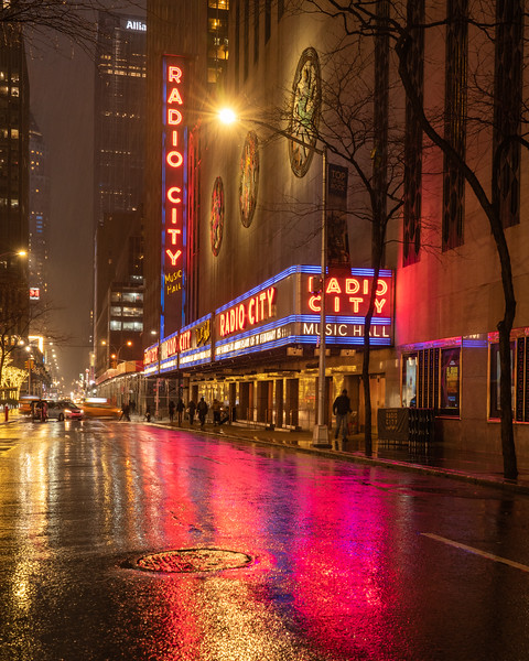 Radio City Music Hall from 50th Street in the rain during the blue hour.