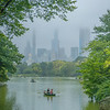 View of a couple in a boat in The Lake in Central Park on a misty day.