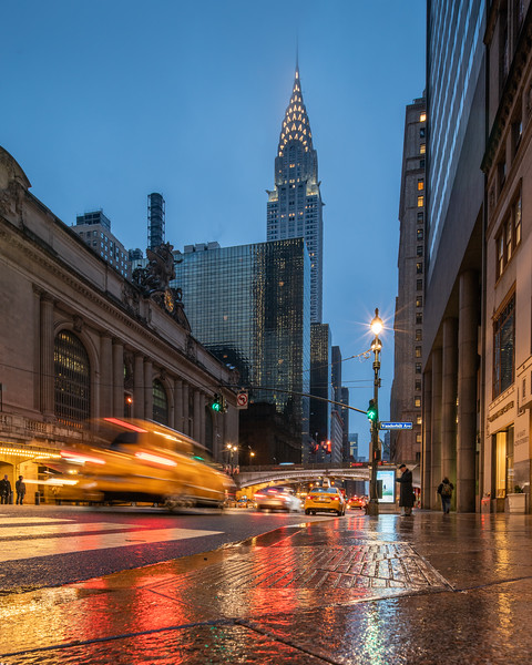 Chrysler Building, Grand Central Terminal, a yellow taxi, and their reflections in the wet sidewalk.