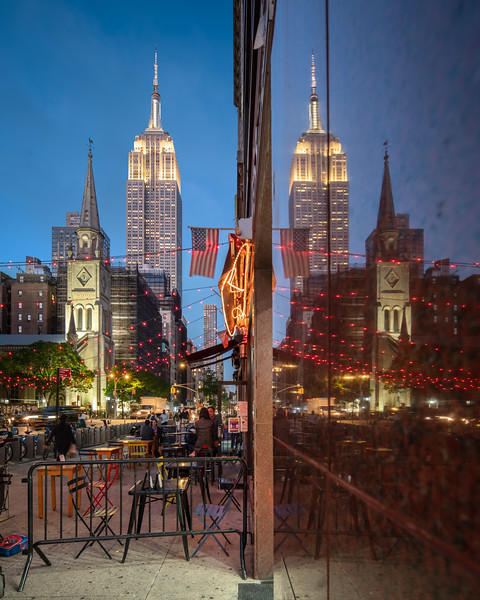 Reflection of the Empire State Building and outdoor dining on 5th Avenue during the blue hour.