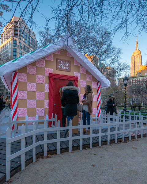 Gingerbread House in Madison Square Park with the Empire State Building at sunset.