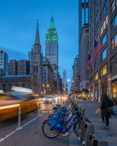 Empire State Building in green, speeding taxi, shopper, and Citibikes at the blue hour.