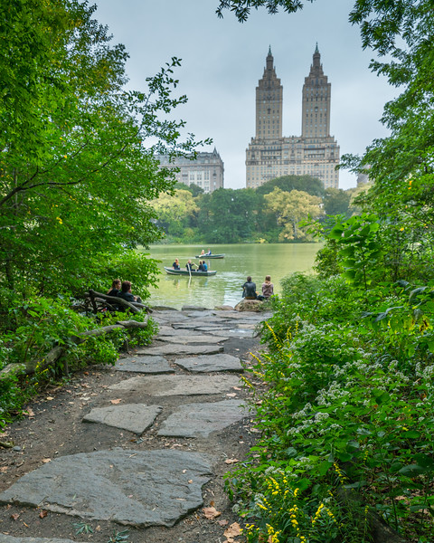 Walking path leading to The Lake and boats in Central Park on a misty day.