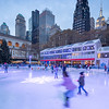 Ice skating in Bryant Park with the Empire State Building and the New York Public Library in the background.