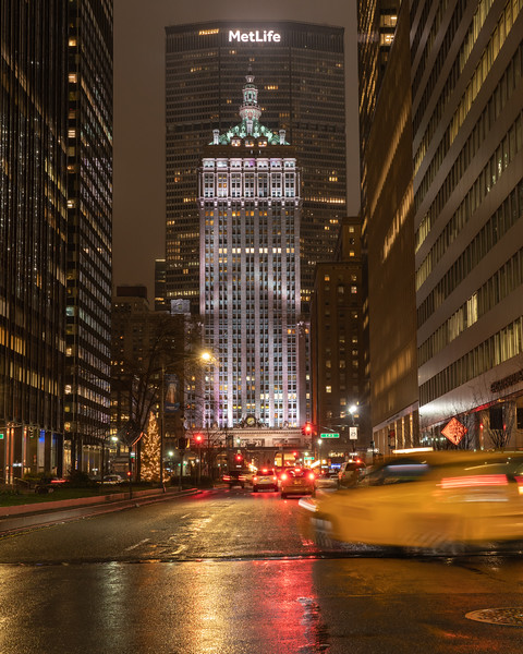 Helmsley Building in white with a taxi on Park Avenue in the rain.