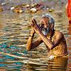 A man saluting the sun god and taking a ritual dip in the Ganga at Varanasi