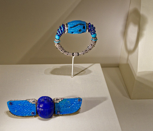 """Scarab brooch, Cartier Paris 1926; gold, platinum, diamonds, sapphires, ancient Egyptian faience scarab, and faience (""""material made from powdered quartz covered with a true vitreous coating, usually in a transparent blue or green isotropic glass""""), Cartier Paris 1926; platinum, faience, enamel, lapis lazuli, turquoise, onyx, and diamonds. Both once owned by Linda Lee Porter,"""