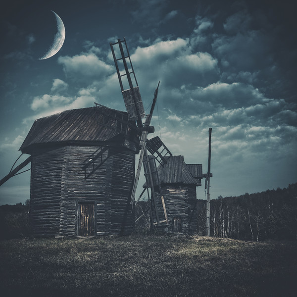 Spooky landscape with few haunted wind mills against dark forest and moody skies