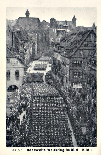 01/1 - NUREMBERG AND MUNICH - CONCESSIONS BY THE GREAT POWERS - NURENBURG, A SYMBOL - A great display of their power for the rulers of the Third Reich came around every autumn. The splendidly staged revue of their party rallies presented in front of the citizens of Nuremberg, the German city where image the splendour of the medieval empire was at its greatest. In almost endless columns marched 120,000 'old fighters' in September 1938 through the decorated streets of the old Nuremburg to the castle, past Adolf Hitler, who watches from his car the parade of SA formations.