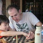 "Mark Choi-Noland and Stu Noland played a game of checkers while attending the Banyan Tree Chai ""Tea Party"""