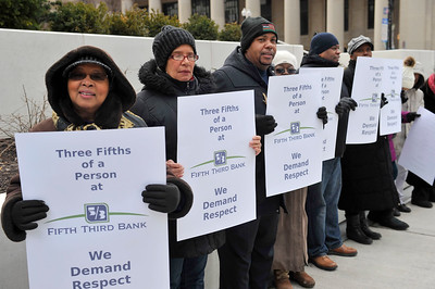FATHER MICHAEL PFLEGER AND THE COMMUNITY OF SAINT SABINA CATHOLIC CHURCH IN THE AUBURN GRESHAM AREA OF SOUTYH CHICAGO DEMONSTRATE IN FRONT OF THE FIFTH THIRD BANK IN DOWNTOWN CHICAGO. PHOTOGRAPHER VALERIE GOODLOE