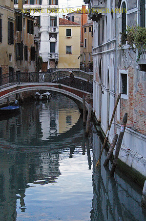 This MIRRORED WATERWAY is one of many in VENICE Italy. Notice the man crossing the footbridge. The weathered walls are real not like the replications that we see in dining establishments in NJ.   VENICE is AWESOME in WINTER.