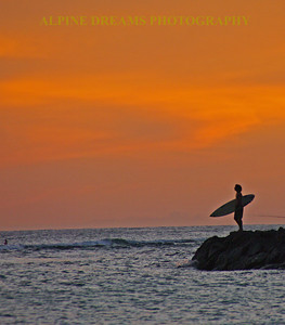This lone surfer is contemplating his dive off the jetty near Diamond Head at sunset ( actually 2 minutes after). Most of the time they jumped in too quickly to setup as they were about 200-300 yards out. THis surfer paused long enough to let me capture this.   They use the jetty to help them to get out past the breakers. This way they get more Runs ( I mean Rides) in to shore. This scene will always be one of my favorites as it is so surreal and the sky was AWESOME!