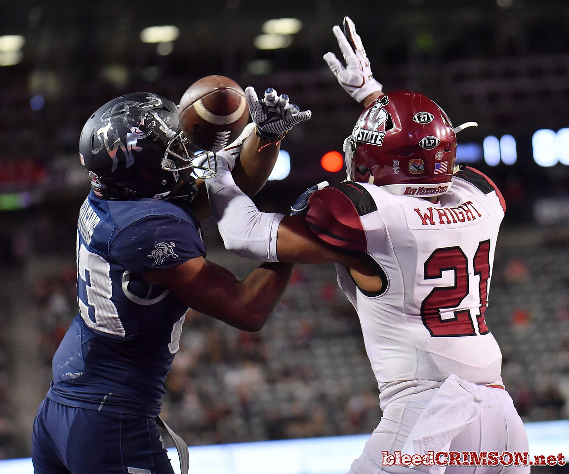 December 29, 2017; Tucson, AZ, USA;  New Mexico State Aggies defensive back Jaden Wright (21) breaks up a pass intended for Utah State Aggies wide receiver Aaren Vaughns (83) during the NOVA Home Loans Arizona Bowl at Arizona Stadium in Tucson, Ariz.  Photo by Sam Wasson/bleedCrimson.net