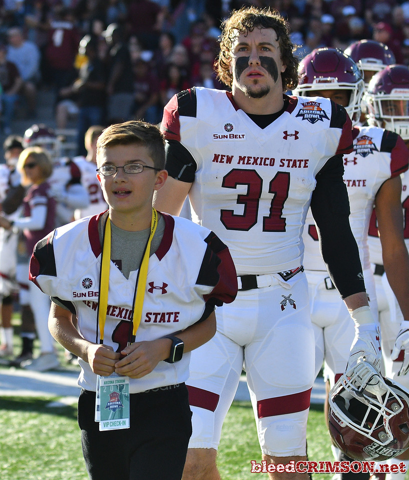 December 29, 2017; Tucson, AZ, USA;  Honorary captain Jeremiah Paulson leads the New Mexico State Aggies onto the field before the team's game against the Utah State Aggies during the NOVA Home Loans Arizona Bowl at Arizona Stadium in Tucson, Ariz.  Photo by Sam Wasson/bleedCrimson.net