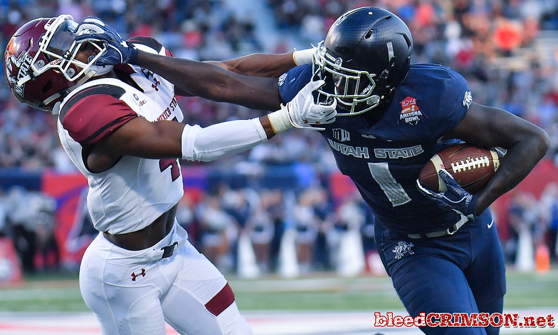 December 29, 2017; Tucson, AZ, USA;  Utah State Aggies wide receiver Ron'quavion Tarver (1) stiff arms New Mexico State Aggies defensive back DeMarcus Owens (4) during the NOVA Home Loans Arizona Bowl at Arizona Stadium in Tucson, Ariz.  Photo by Sam Wasson/bleedCrimson.net