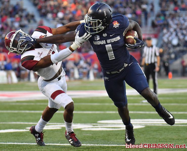 December 29, 2017; Tucson, AZ, USA;  New Mexico State Aggies defensive back DeMarcus Owens (4) tries to tackle Utah State Aggies wide receiver Ron'quavion Tarver (1) during the NOVA Home Loans Arizona Bowl at Arizona Stadium in Tucson, Ariz.  Photo by Sam Wasson/bleedCrimson.net