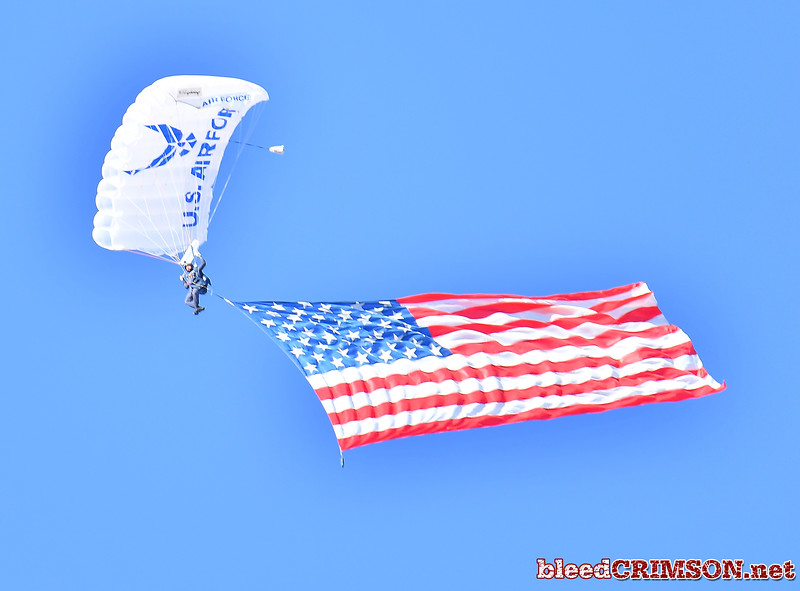 December 29, 2017; Tucson, AZ, USA;  A member of the Wings of Blue parachute team flies over the stadium with a giant American flag before the NOVA Home Loans Arizona Bowl game between the New Mexico State Aggies and the Utah State Aggies at Arizona Stadium in Tucson, Ariz.  Photo by Sam Wasson/bleedCrimson.net