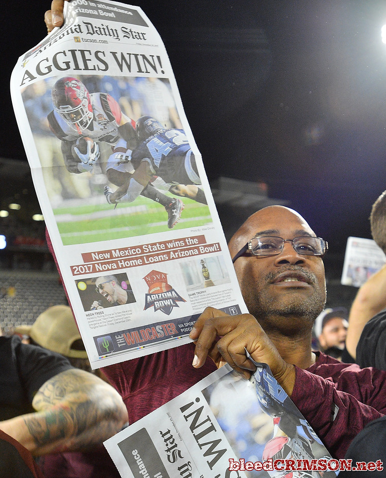 December 29, 2017; Tucson, AZ, USA;  A fan holds up a commemorative paper after the New Mexico State Aggies won the NOVA Home Loans Arizona Bowl over the Utah State Aggies at Arizona Stadium in Tucson, Ariz.  Photo by Sam Wasson/bleedCrimson.net