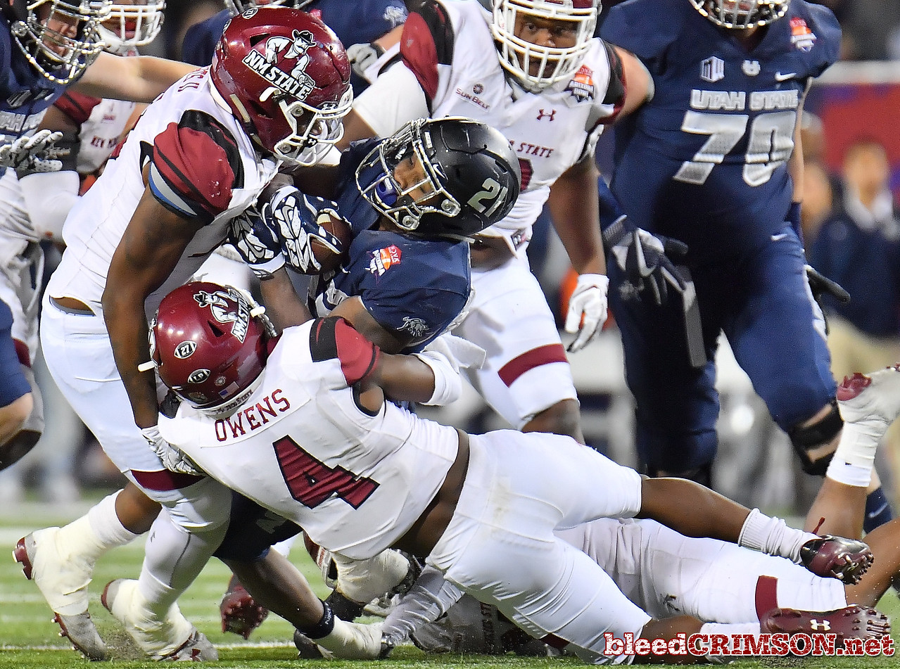 December 29, 2017; Tucson, AZ, USA;  New Mexico State Aggies defensive lineman Cedric Wilcots II (10) and defensive back DeMarcus Owens (4) tackle Utah State Aggies running back LaJuan Hunt (21) during the NOVA Home Loans Arizona Bowl at Arizona Stadium in Tucson, Ariz.  Photo by Sam Wasson/bleedCrimson.net