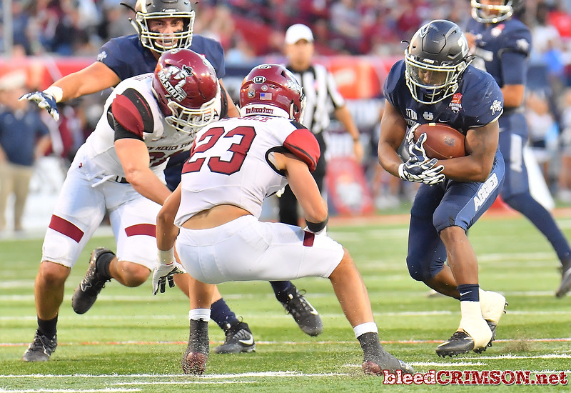 December 29, 2017; Tucson, AZ, USA;  New Mexico State Aggies defensive back Ron LaForce (23) defends Utah State Aggies running back LaJuan Hunt (21) during the NOVA Home Loans Arizona Bowl at Arizona Stadium in Tucson, Ariz.  Photo by Sam Wasson/bleedCrimson.net