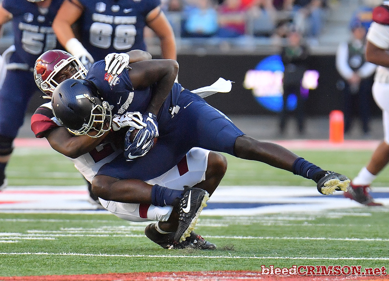 December 29, 2017; Tucson, AZ, USA;  New Mexico State Aggies defensive back Shamad Lomax (22) tackles Utah State Aggies wide receiver Ron'quavion Tarver (1) during the NOVA Home Loans Arizona Bowl at Arizona Stadium in Tucson, Ariz.  Photo by Sam Wasson/bleedCrimson.net