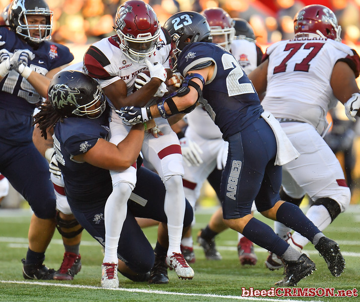 December 29, 2017; Tucson, AZ, USA;  New Mexico State Aggies running back Jason Huntley (1) is tackled by Utah State Aggies safety Gaje Ferguson (23) and Utah State Aggies nose tackle Christopher 'Unga (96) during the NOVA Home Loans Arizona Bowl at Arizona Stadium in Tucson, Ariz.  Photo by Sam Wasson/bleedCrimson.net