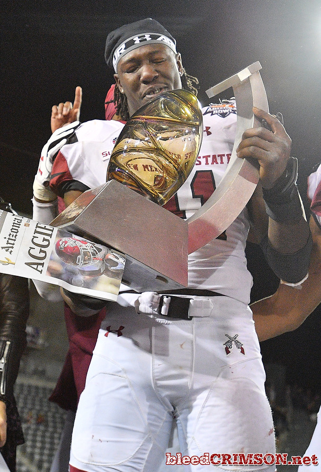 December 29, 2017; Tucson, AZ, USA;  New Mexico State Aggies linebacker Leon McQuaker (41) holds at the championship trophy after his team defeated the Utah State Aggies 26-20 in overtime at the NOVA Home Loans Arizona Bowl at Arizona Stadium in Tucson, Ariz.  Photo by Sam Wasson/bleedCrimson.net