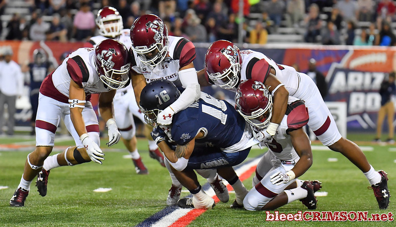 December 29, 2017; Tucson, AZ, USA;  (L-R) New Mexico State Aggies defensive lineman Cedric Wilcots II (10), defensive back Josh Aganon (6), linebacker Jonathan Hood (20) and defensive back Austin Shaw (13) tackle Utah State Aggies wide receiver Jordan Nathan (16) during the NOVA Home Loans Arizona Bowl at Arizona Stadium in Tucson, Ariz.  Photo by Sam Wasson/bleedCrimson.net