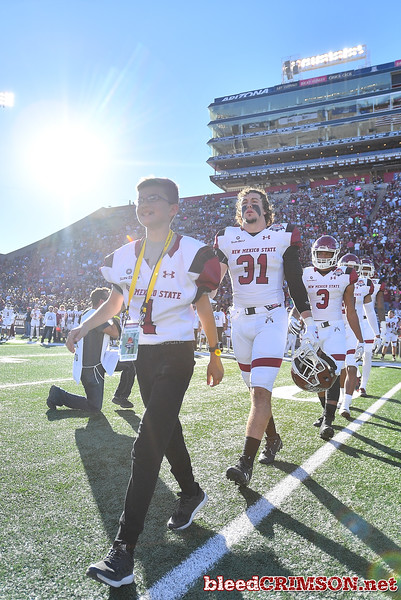 December 29, 2017; Tucson, AZ, USA;  New Mexico State Aggies honorary captain Jeremiah Paulson leads the Aggie captains out to the coin toss before the team's game against the Utah State Aggies during the NOVA Home Loans Arizona Bowl at Arizona Stadium in Tucson, Ariz.  Photo by Sam Wasson/bleedCrimson.net