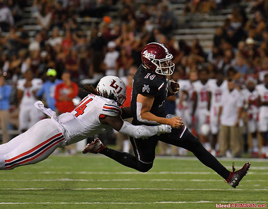 LAS CRUCES, NEW MEXICO - OCTOBER 05, 2019:  Quarterback Josh Adkins #14 of the New Mexico State Aggies runs for a gain against linebacker Solomon Ajayi #14 of the Liberty Flames during their game at Aggie Memorial Stadium on October 05, 2019 in Las Cruces, New Mexico.The Flames defeated the Aggies 20-13.  (Photo by Sam Wasson)