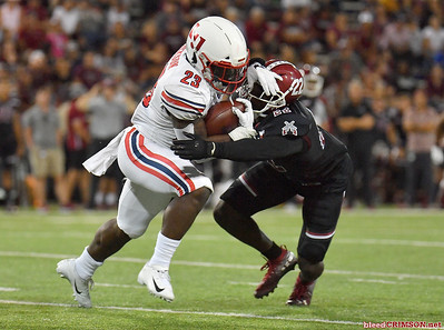LAS CRUCES, NEW MEXICO - OCTOBER 05, 2019:  Defensive back Shamad Lomax #22 of the New Mexico State Aggies tackles running back Frankie Hickson #23 of the Liberty Flames during their game at Aggie Memorial Stadium on October 05, 2019 in Las Cruces, New Mexico.  (Photo by Sam Wasson)