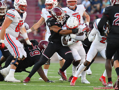 LAS CRUCES, NEW MEXICO - OCTOBER 05, 2019:  Linebacker Javahn Fergurson #7 of the New Mexico State Aggies tackles running back Frankie Hickson #23 of the Liberty Flames during their game at Aggie Memorial Stadium on October 05, 2019 in Las Cruces, New Mexico.The Flames defeated the Aggies 20-13.  (Photo by Sam Wasson)