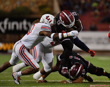 LAS CRUCES, NEW MEXICO - OCTOBER 05, 2019:  wide receiver Tony Nicholson #13 of the New Mexico State Aggies is tackled safety Rion Davis #3 of the Liberty Flames by during their game at Aggie Memorial Stadium on October 05, 2019 in Las Cruces, New Mexico.The Flames defeated the Aggies 20-13.  (Photo by Sam Wasson)