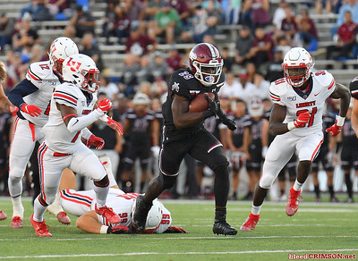 LAS CRUCES, NEW MEXICO - OCTOBER 05, 2019:  Running back Christian Gibson #25 of the New Mexico State Aggies runs for a gain against cornerback Tayvion Land #7 and safety Elijah Benton #31 of the Liberty Flames during their game at Aggie Memorial Stadium on October 05, 2019 in Las Cruces, New Mexico.  (Photo by Sam Wasson)
