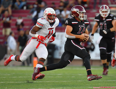 LAS CRUCES, NEW MEXICO - OCTOBER 05, 2019:  quarterback Josh Adkins #14 of the New Mexico State Aggies runs for a gain against defensive lineman Jessie Lemonier #11 of the Liberty Flames during their game at Aggie Memorial Stadium on October 05, 2019 in Las Cruces, New Mexico.  (Photo by Sam Wasson)