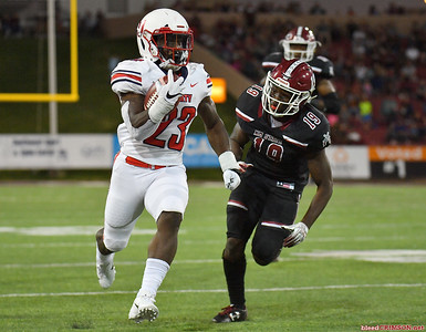 LAS CRUCES, NEW MEXICO - OCTOBER 05, 2019:  Running back Frankie Hickson #23 of the Liberty Flames runs for a gain against defensive back Austin Perkins #19 of the New Mexico State Aggies during their game at Aggie Memorial Stadium on October 05, 2019 in Las Cruces, New Mexico.  (Photo by Sam Wasson)