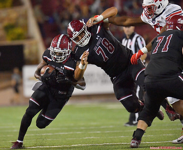 LAS CRUCES, NEW MEXICO - OCTOBER 05, 2019:  wide receiver Tony Nicholson #13 runs past offensive lineman Brian Trujillo #78 of the New Mexico State Aggies during their game against the Liberty Flames at Aggie Memorial Stadium on October 05, 2019 in Las Cruces, New Mexico.  (Photo by Sam Wasson)