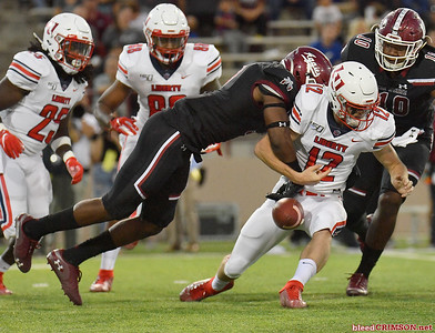 LAS CRUCES, NEW MEXICO - OCTOBER 05, 2019:  Linebacker Devin Richardson #3 of the New Mexico State Aggies forces a fumble against quarterback Stephen Calvert #12 of the Liberty Flames during their game at Aggie Memorial Stadium on October 05, 2019 in Las Cruces, New Mexico.The Flames defeated the Aggies 20-13.  (Photo by Sam Wasson)