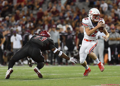LAS CRUCES, NEW MEXICO - OCTOBER 05, 2019:  Quarterback Stephen Calvert #12 of the Liberty Flames runs for a gain against linebacker Rashie Hodge Jr. #23 of the New Mexico State Aggies during their game at Aggie Memorial Stadium on October 05, 2019 in Las Cruces, New Mexico.  (Photo by Sam Wasson)