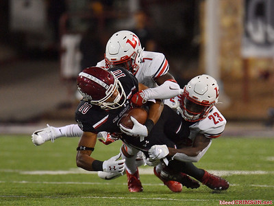 LAS CRUCES, NEW MEXICO - OCTOBER 05, 2019:  Wide receiver Izaiah Lottie #10 of the New Mexico State Aggies is tackled by cornerback Tayvion Land #7 and cornerback Kei'Trel Clark #23 of the Liberty Flames during their game at Aggie Memorial Stadium on October 05, 2019 in Las Cruces, New Mexico.The Flames defeated the Aggies 20-13.  (Photo by Sam Wasson)