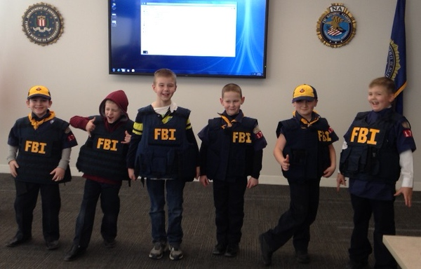 . A photo from 2015 showing members of Cub Scouts Pack 1786, Den 5 during their visit to the Detroit Division of the FBI. The scouts learned about what the FBI investigates, how to become an FBI agent, and how to collect evidence like fingerprints. Parents and scouts also had an opportunity to try on FBI ballistic vests and other tactical gear.