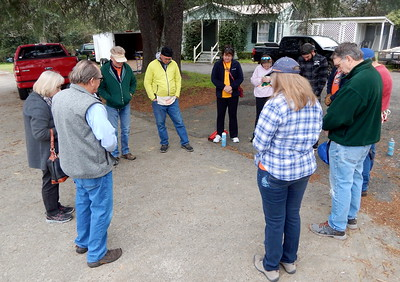 Volunteers pray before starting their work at Fuller Center headquarters Monday.