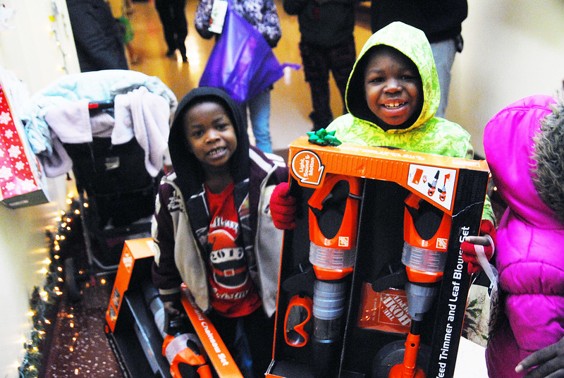 Children in Chicago smile and hold gifts, courtesy of the CHIP Program through Life Builders United. The program was held Dec. 23 at Old Masonic Hall and over 400 children received free gifts and food.