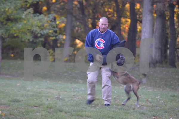 Officer Paul Samuelson, who trains police dogs, helps demonstrate the canine's skills.