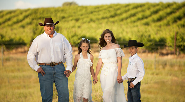 Beautiful family photo by the vineyard.